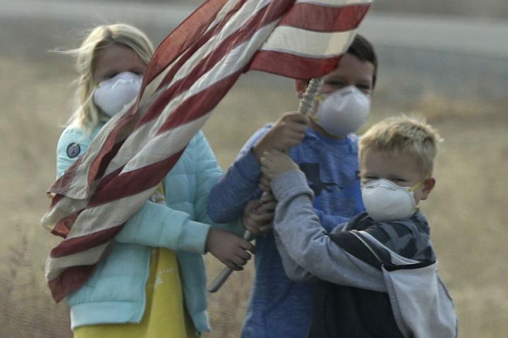 Kinder mit Mundschutz stehen am Straßenrand.