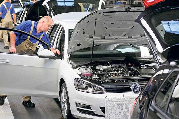 Ein Mitarbeiter von Volkswagen Sachsenkontrolliert einen Golf VII in der Endmontage.