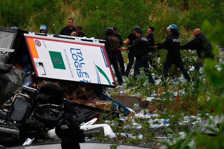 Rettungsarbeiten unter den Trümmern der eingestürzten Morandi Autobahnbrücke.