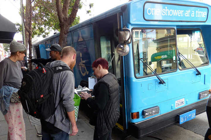 """Obdachlose werden in San Francisco in die Warteliste für den mobilen Dusch-Bus mit der Aufschrift """"One Shower at a Time"""" eingetragen."""