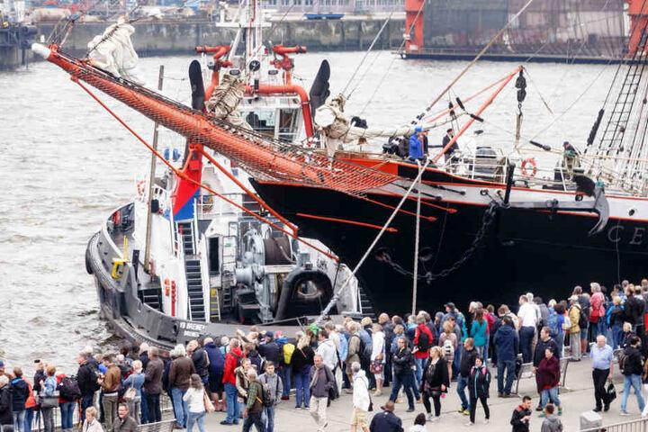 Besucher des Hafengeburtstags beobachten nach der Einlaufparade das Anlegemanöver des russischen Großseglers Sedov an den Landungsbrücken.