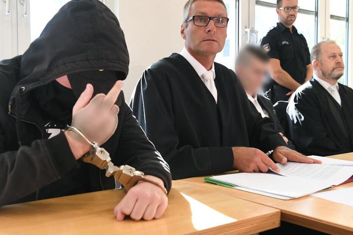 Der 19-jähriger Angeklagte (l) zeigt im Gerichtssaal im Landgericht den Mittelfinger.