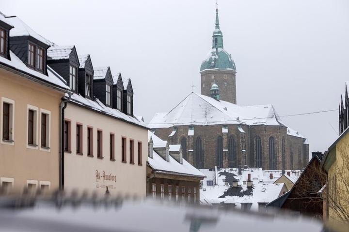 Im Erzgebirge hat es einige Zentimeter Neuschnee gegeben. Die Dächer um die St. Annen Kirche in Annaberg-Buchholz sind verschneit.