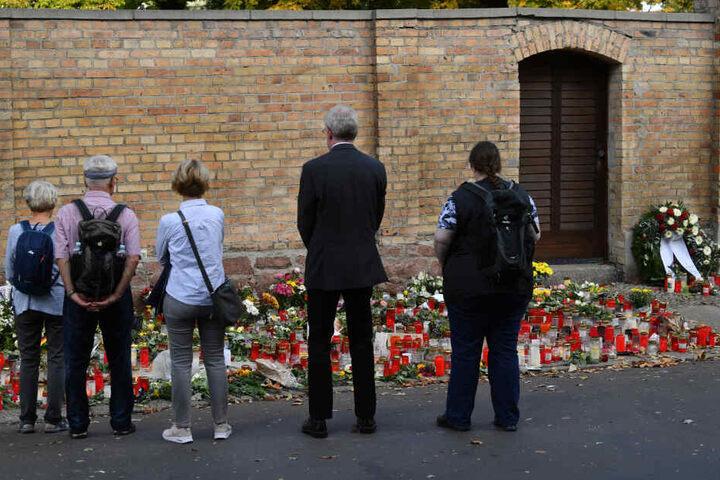Menschen stehen in Halle nach dem rechtsextremistischen Anschlag vor niedergelegten Kerzen und Blumen an der Synagoge.