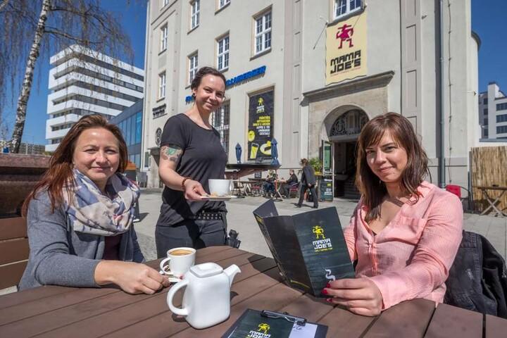 Tina Langer (30) bedient Daniela Lenk (l.) und Carolin Naumann im neuen Freiluftcafé des Mama Joe's am Johannisplatz.
