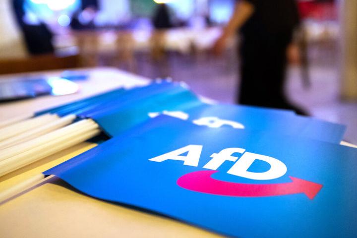 Fähnchen mit dem Logo der AfD liegen beim Landesparteitag der AfD Bayern auf einem Tisch.
