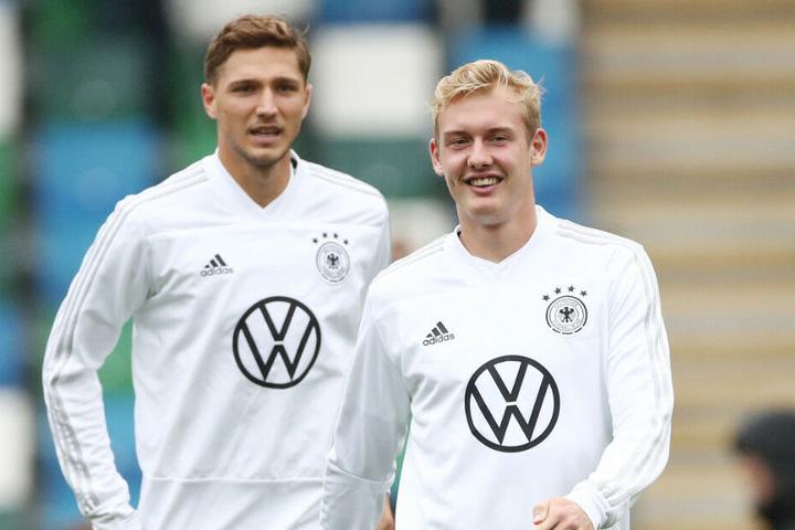 Julian Brandt (r.) und Niklas Stark wärmen sich vor dem Spiel in Nordirland auf.