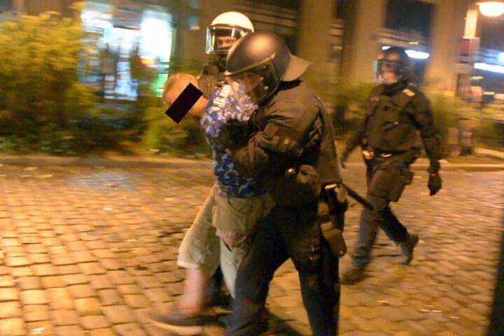 Polizisten führen einen der Krawallos ab.