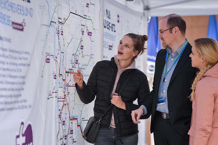 """Gut getaktet ins Umland: VVO-Sprecher Christoph Schlemper erklärt zwei Besucherinnen des Mobilitätstages das """"PlusBus""""-Konzept."""