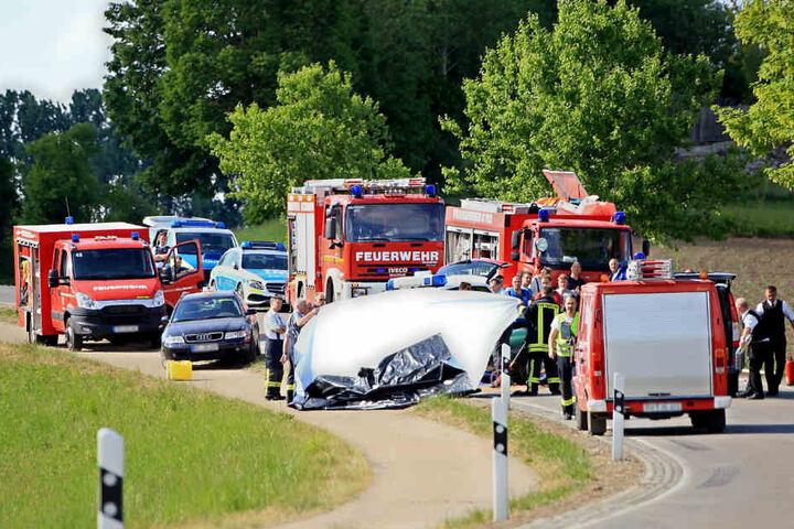 Die Unfallstelle bei Ebenweiler am Mittwoch. Einsatzkräfte schirmen das Wrack des Porsche ab.