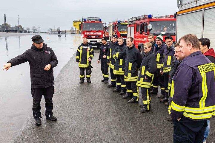 Alles klar? Fahrlehrer Sven Förster (52, u.l.) weist die Feuerwehr-Fahrer auf der Nass-Strecke ein.