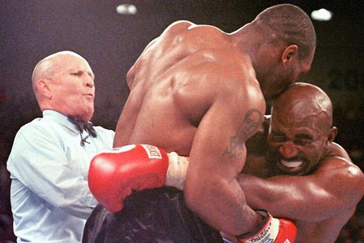 Aufsehenerregende Szene 1997: Mike Tyson (Mitte) beißt Evander Holyfield (rechts) ins Ohr.
