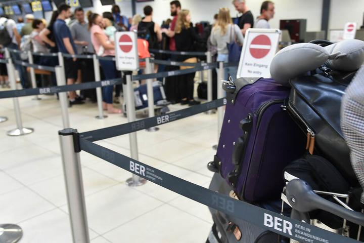 Urlauber stehen im Flughafen Berlin-Schönefeld an den Check-in Schaltern.