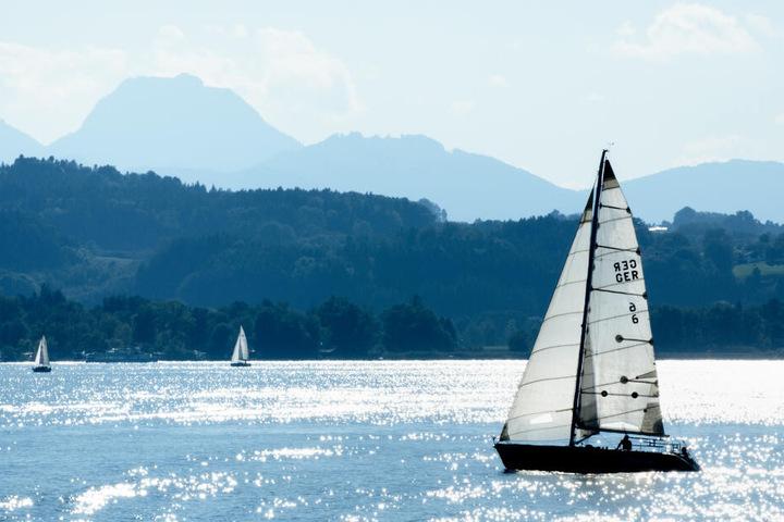 Das Wasser auf dem Chiemsee glitzert rund um ein Segelboot.