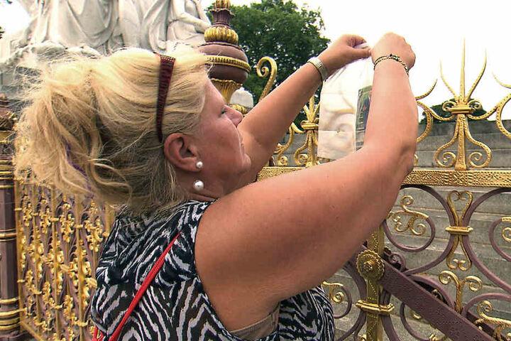 Prinzessina-Diana-Fan Silvia hängt eine Karte an den Zaun des Kensington Palasts.