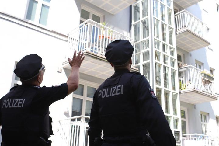 Zwei Polizisten stehen vor dem Fahrstuhl des Wohnhauses.