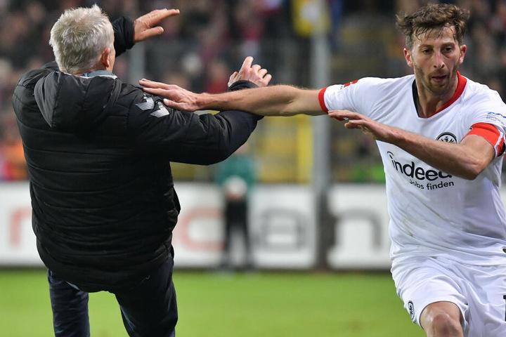 Trainer Christian Streich (SC Freiburg) wird von David Abraham (Eintracht Frankfurt) umgerannt.