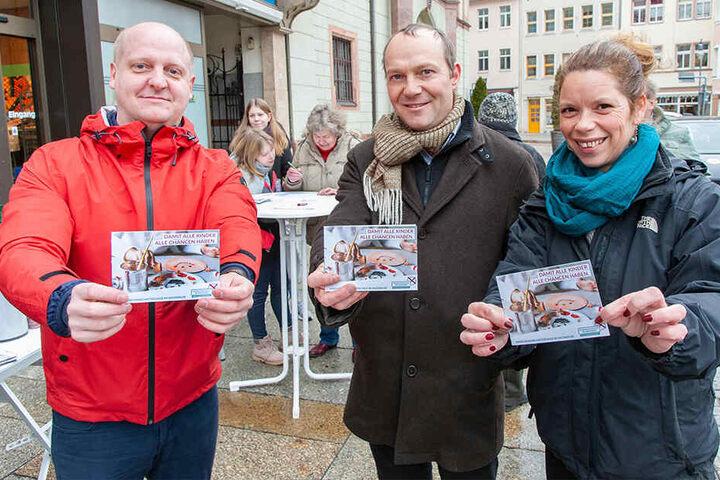 Henning Homann (SPD, l.), Wolfram Günther (Grüne) und Antje Feiks (Linke) zeigen den Schul-Antrag.