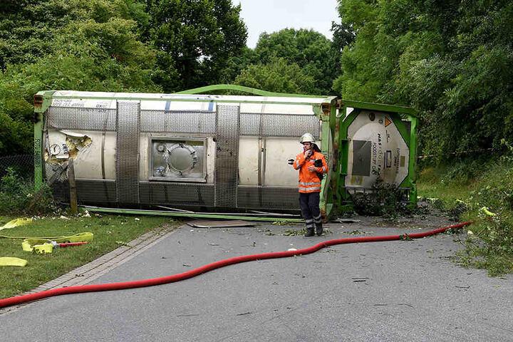 Ein Feuerwehrmann steht vor zwei verunglückten Güter-Waggons.