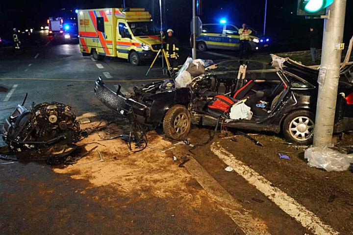 Einsatzkräfte am Unfallort hinter dem Wrack des Audi.