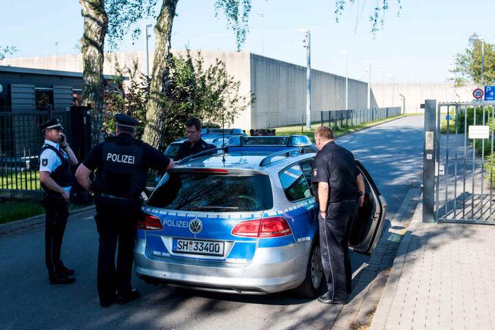 Polizeibeamte stehen vor der Justizvollzugsanstalt in Lübeck: Ein Geiselnehmer hat hier eine Frau in seine Gewalt gebracht, wie ein Sprecher des Justizministeriums erklärte.