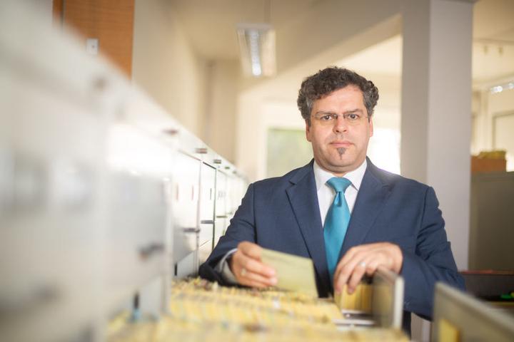 Jens Rommel, Behördenleiter, steht im Archiv der Zentralen Stelle an einer Schublade mit Karteikarten.