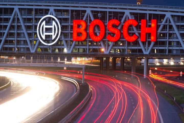 Unter einer Autobahnbrücke mit dem Bosch-Logo fahren Autos.