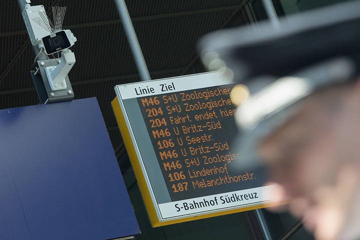 Ein Bundespolizist steht vor einer Überwachungskamera im Bahnhof Südkreuz.