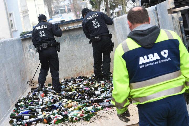 Polizisten durchsuchen in Zinnowitz einen Altglascontainer. Im ungelösten Mordfall einer 18-Jährigen sucht die Polizei nach neuen Spuren auf der Insel Usedom.