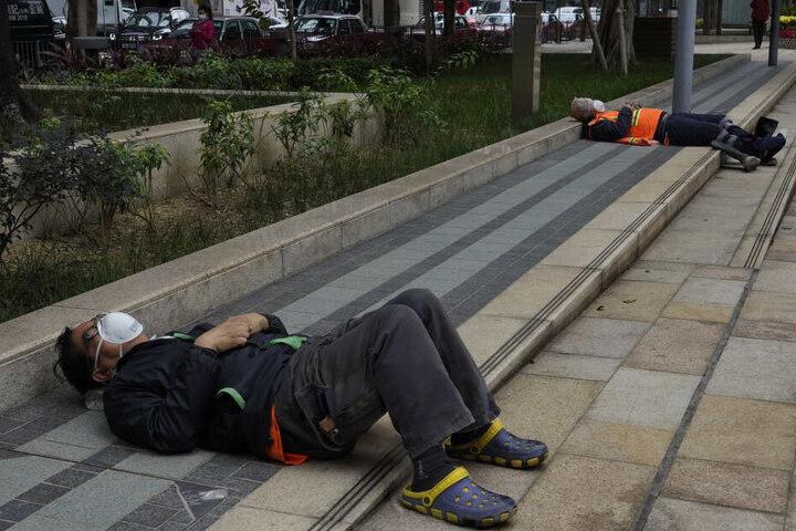 Zwei Arbeiter tragen Mundschutz, während sie sich in einem Park ausruhen.