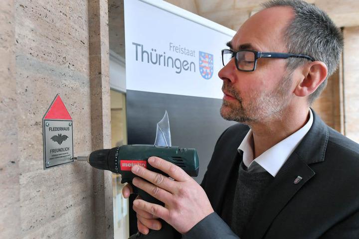 Olaf Möller, Staatssekretär im Thüringer Ministerium für Umwelt, Energie und Naturschutz, schraubt die Auszeichnungs-Plakette an eine Mauer des Umweltministeriums.