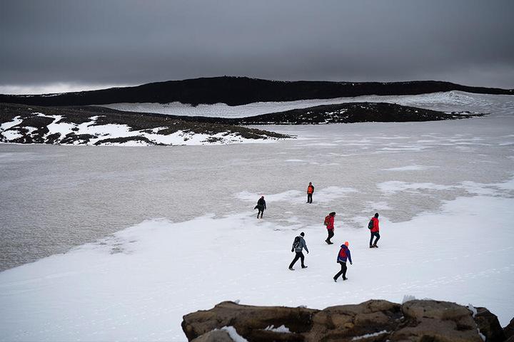 Zahlreiche Menschen wandern über die Reste des Okjökull zu einer Gedenkveranstaltung für den vergangenen Gletscher.