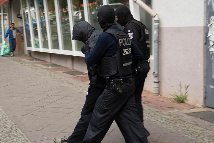 Polizeibeamte führen einen der Verdächtigen mit Handschellen ab.