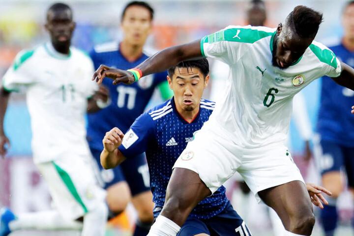 Der baldige Schalker Salif Sané (Senegal; vorne) im Duell mit Dortmund Shinji Kagawa (Japan; hinten).