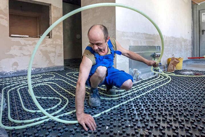 Baustelle Stadtbad: Handwerker Thomas Mehnert (50) verlegt die Leitung für  die Fußbodenheizung.