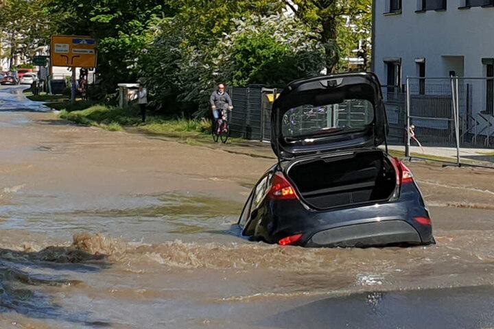 Das Auto steckt bis zur Hälfte im Loch.
