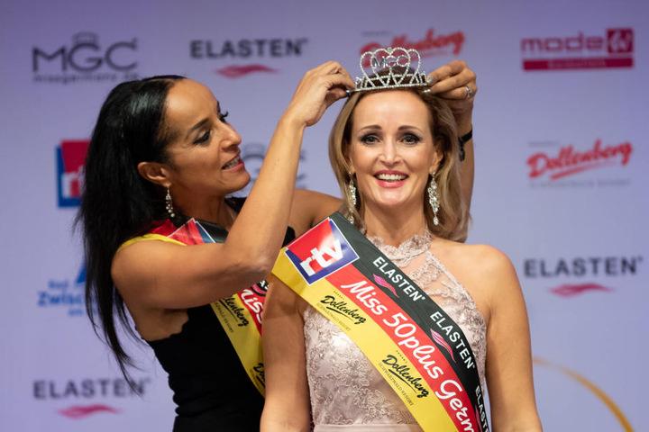 Evelyn Reißmann (r), Siegerin bei Miss 50plus Germany, bekommt von der Vorjahressiegerin Manuela Thoma-Adofo ihr Diadem aufgesetzt.