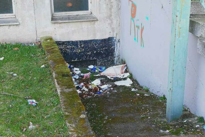 Müll liegt neben dem Eingangsbereich zur 84. Schule.