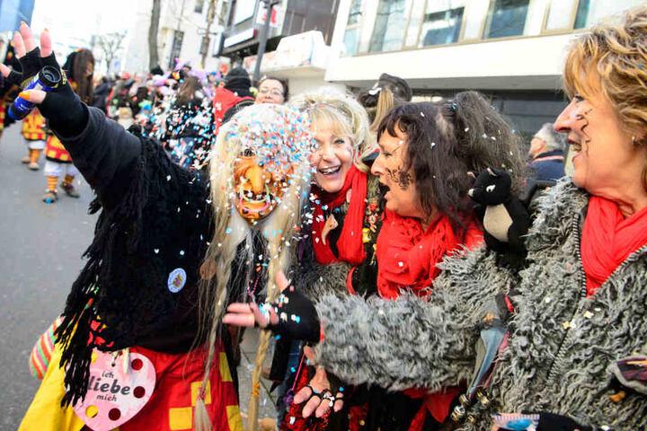 Ein Narr mit Maske und Zuschauer feiern beim großen Faschingsumzugdurch die Stuttgarter Innenstadt.