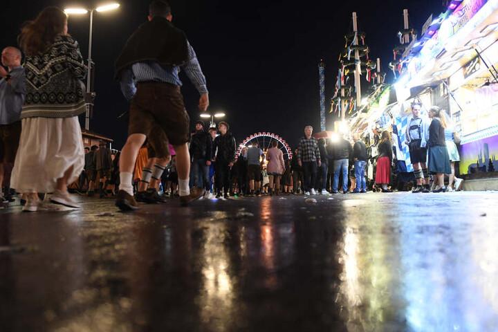 Die Lichter der Wiesn spiegeln sich auf dem nassen Straße auf der Theresienwiese. Am zweiten Wochenende kann es in München regnen.