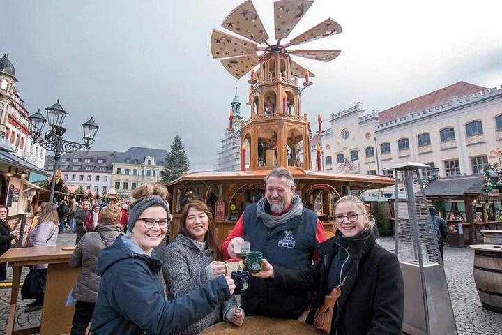 Ralf Schwartz (57), Chef der Glühweinpyramide, begrüßt die ersten Gäste auf dem Weihnachtsmarkt: Tina Kratzsch (23), Linh Nguyen (25) und Sarah-Marie Reichardt (22, von links) aus Thüringen.