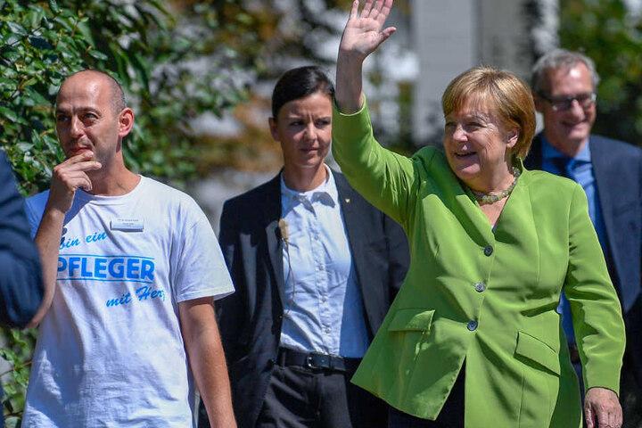 Bundeskanzlerin Angela Merkel winkt neben Pfleger Ferdi Cebi.