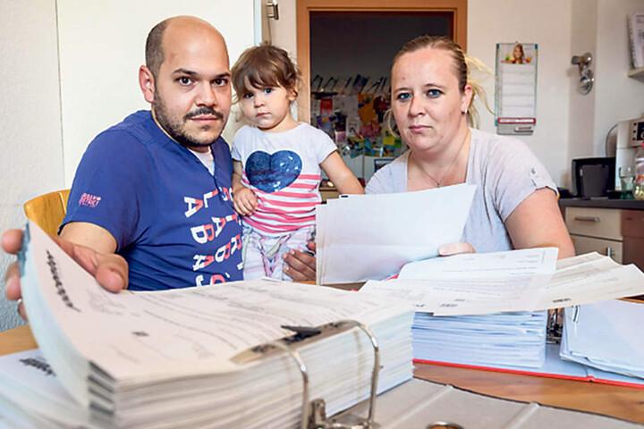 Thilo Hahn (38), Tochter Leila (2) und Mama Nicole Hahn (33) sitzen vor riesigen Aktenbergen.