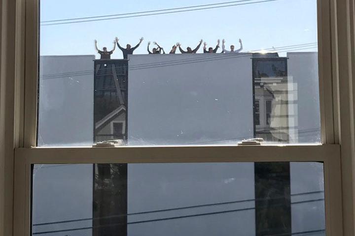 Mitarbeiter von UPS winken vom Dach nach einer Schießerei in der Zweigstelle des Paketdienstes.