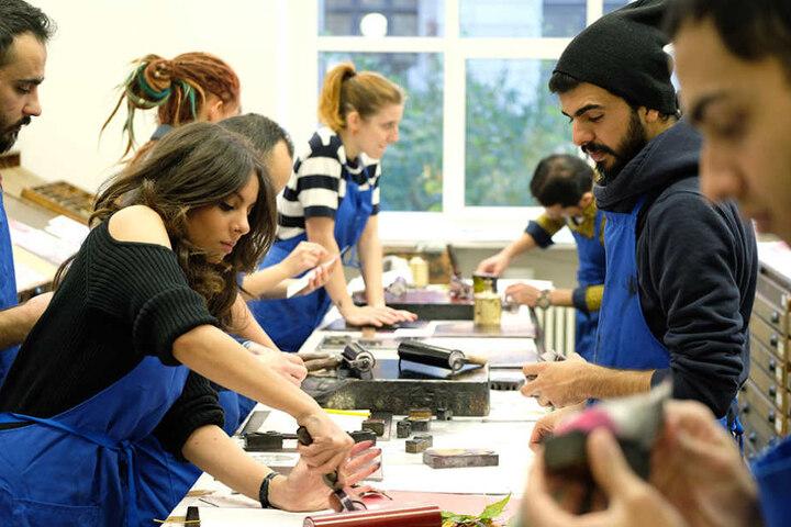 Studenten der HGB, darunter auch Flüchtlinge,  arbeiten in der Druckwerkstatt.