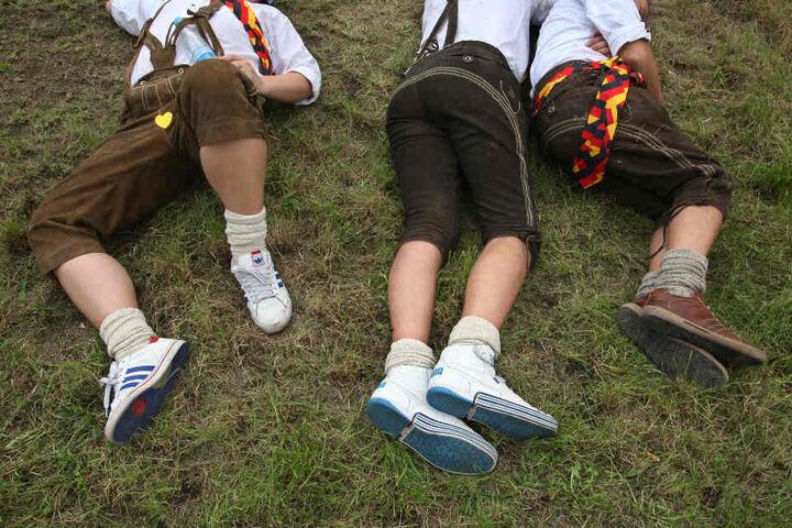 Lederhose, Turnschuhe und jede Menge Promille: Drei junge Männer schlafen auf dem Oktoberfest ihren Rausch aus.