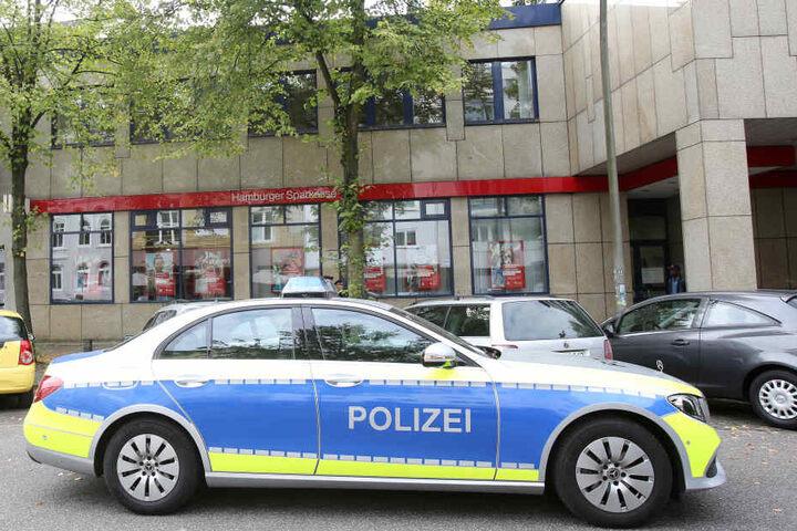 Ein Polizeiwagen steht nach einem Banküberfall an der Rückseite der Filiale.