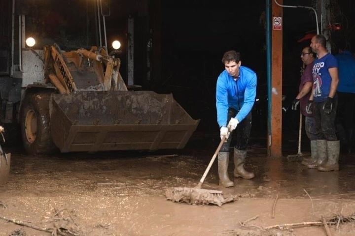 Der spanische Tennisspieler Rafael Nadal räumt mit den Bewohnern den Schlamm aus ihren Häusern.