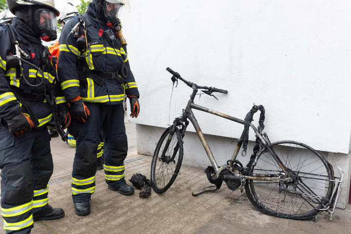 Zwei mit Atemschutzmasken bekleidete Feuerwehrmänner gucken sich das zerstörte E-Bike an.