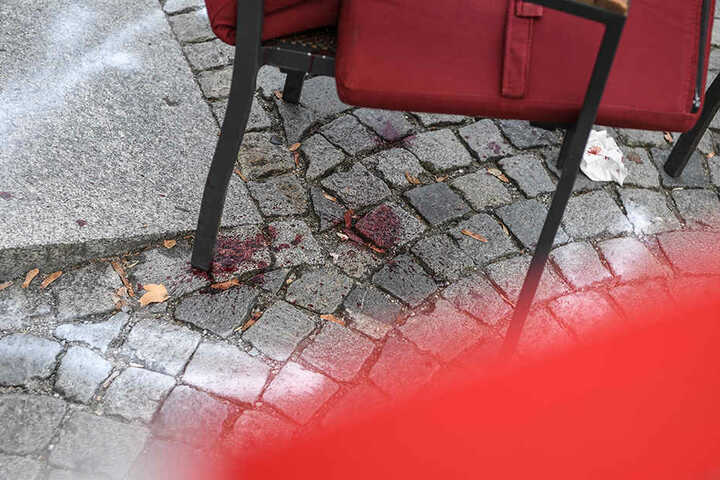 Der Bereich um einen Stuhl ist im abgesperrten Tatort auf dem Marienplatz markiert. Darunter ist Blut von der Messerstecherei zu sehen.